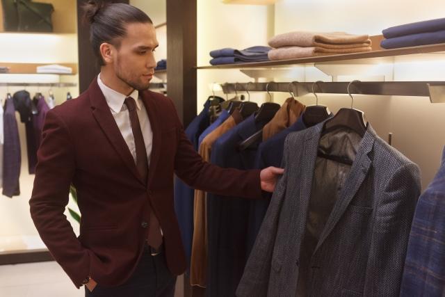 紳士服店でスーツを選ぶ男性