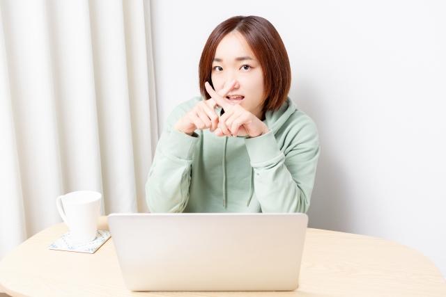 ノートパソコンを使いながらNGのジェスチャーをする女性