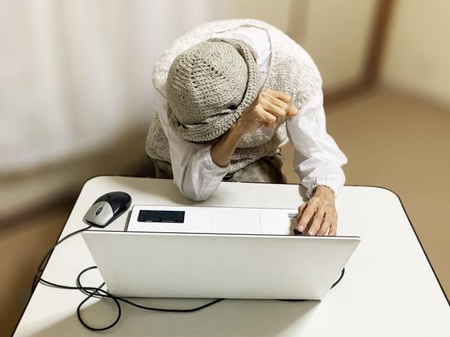 ノートパソコンの前で悩む高齢女性