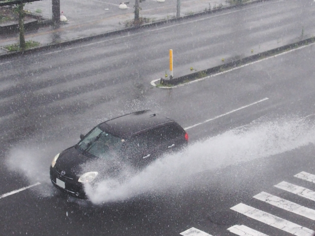 冠水した道路で水しぶきを上げて走る一台の黒い車